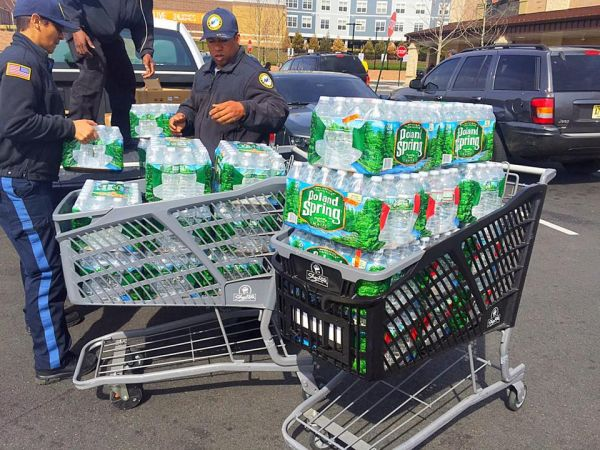 NPA maintenance officers packing the water in the pickup truck — at ShopRite of Newark - Springfield Ave. Marketplace.